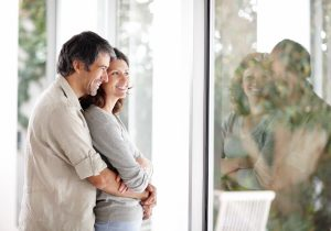 Cosy mature couple standing near a window at home